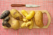 Assorted types of potato on a chopping board