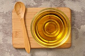 Olive oil in a glass dish on a chopping board with a wooden spoon