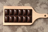 A bar of chocolate on a chopping board