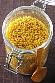 Lots of elbow macaroni in a storage glass