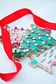 A decorated biscuit in the shape of a Christmas tree, and a red gift ribbon
