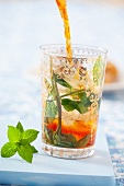 Iced tea being poured into a glass with ice cubes and mint
