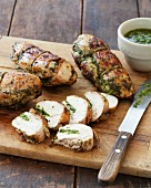 Grilled Pesto Chicken Breasts on a Cutting Board; One Sliced