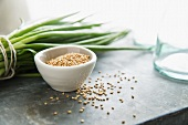 A Bowl of Sesame Seeds with Some Spilled; Green Onions in Background
