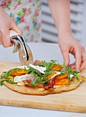 A woman cutting in half a pizza topped with rocket, prosciutto, goat's cheese and tomatoes