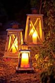 Laternen mit Kerzen auf einem Gartenweg als abendliche Beleuchtung