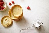 Freshly baked tartlets ready for filling, next to them raspberries and powdered sugar
