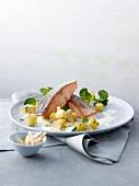 Lachsforellenfilets mit Haut auf Kartoffelwürfeln mti Mandeln