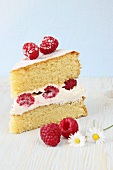 A slice of sponge cake with whipped cream and fresh raspberries