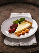 A slice of cheese cake with raspberries and blackberry ice cream