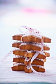 Pile of gingerbread stars garnished with icing and tied with ribbon
