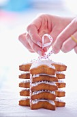 Woman tiding a pile of gingerbread stars garnished with icing