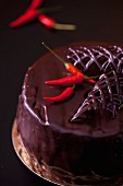 Chocolate chili cake covered with dark chocolate and garnished with small chili peppers
