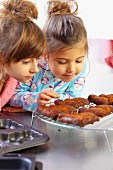 Zwei Mädchen betrachten frisch gebackene Möhrenplätzchen