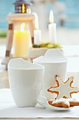 Gingerbread stars with white icing and white cups in front of candles