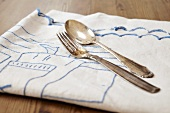 A silver fork and a silver spoon on a tea towel