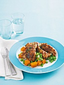 Chicken pieces with a honey and mustard crust on a bed of vegetables
