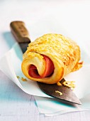 A puff pastry roll filled with ham and cheese