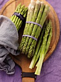 Green asparagus, bundled, on a chopping board