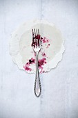 The remains of berry cake on a paper doily