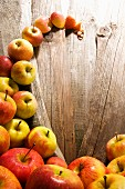 A wave of bedewed apples (Elstar, Jonagold) on rustic wood boards
