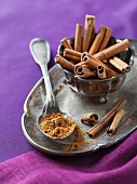 Cinnamon sticks and ground cinnamon on a silver tray