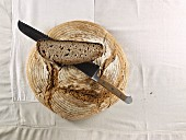 A brown loaf, with a bread knife and a slice of bread lying on top of it