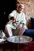 Nordafrikaner giesst Tee in Gläser