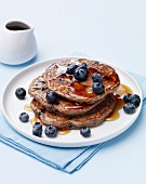Buckwheat Blueberry Pancakes with Maple Syrup on a White Plate
