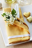 A napkin as a cutlery pocket decorated with elderflowers