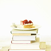 A slice of strawberry cake on a stack of books