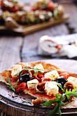 Pizzastück mit Oliven, Feta und Anchovis