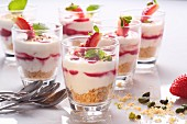 Layered strawberry dessert with pistachios and a crumb base