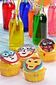 Cupcakes mit Superheldmotiven verziert und bunte Getränke mit Strohalm in Flaschen