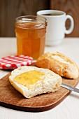 A bread roll spread with elderflower jam