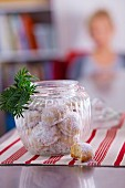 Butter biscuits in a storage jar with a sprig of fir