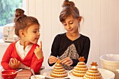 Two girls decorating Christmas trees made from stacked Lebkuchen (spiced soft gingerbread from Germany)