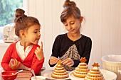 Zwei Mädchen verzieren Lebkuchenchristbäume