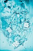 Eiswürfel fallen ins Wasser