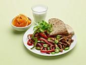 Schweinefleisch-Fajita mit Orangen und einem Glas Milch
