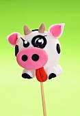 A cake pop decorated to look like a cow