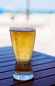Glass of Cold Beer on an Outdoor Table at the Beach