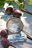 Plums with icing sugar and a sieve