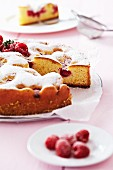 Raspberry cake with icing sugar, partly sliced