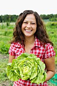 Portrait of young woman holding cabbage in allotment