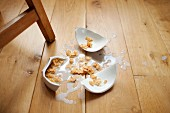 Broken bowl of cereal on wooden floor