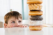 A small boy looking over the edge of a table at a stack of baked goods