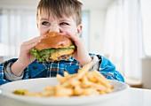 A boy biting into a hamburger