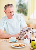 A man sitting at a breakfast table reading a newspaper