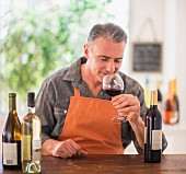 A man with an apron tasting wine